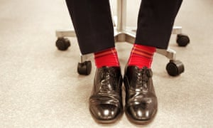 Businessman sitting on office chair wearing red socks