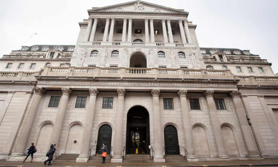 People walk past the Bank of England on Threadneedle Street in the City of London