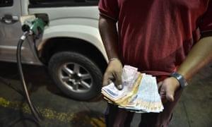 A petrol station attendant counts Venezuelan bolivar banknotes.