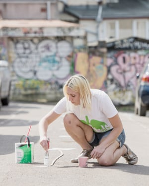 Jen Law paints social distancing markers on the road.