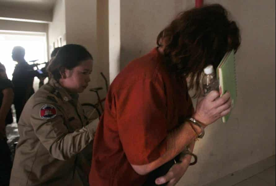Tammy Davis-Charles (right), hides her face as she enters the Phnom Penh municipal court.