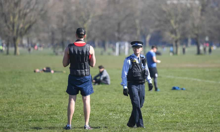 A police community support officer speaks to people exercising on Clapham Common, south London