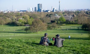 Members of the public enjoy the day's warm weather on Primrose Hill on Saturday in London, England