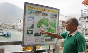Tour boat operator Wong Yung-kan pointing out where the famous pink dolphins are found in the waters around Tai O in Hong Kong.