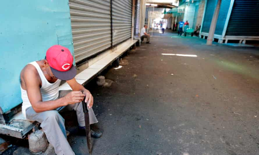 A guard sits next to closed stalls Friday in the latest nationwide 24-hour general strike in Managua, Nicaragua.