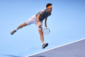 Dominic Thiem gives it his all as he serves to Novak Djokovic.