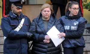 Mariangela Di Trapani is escorted by officers during a police operation in Palermo.