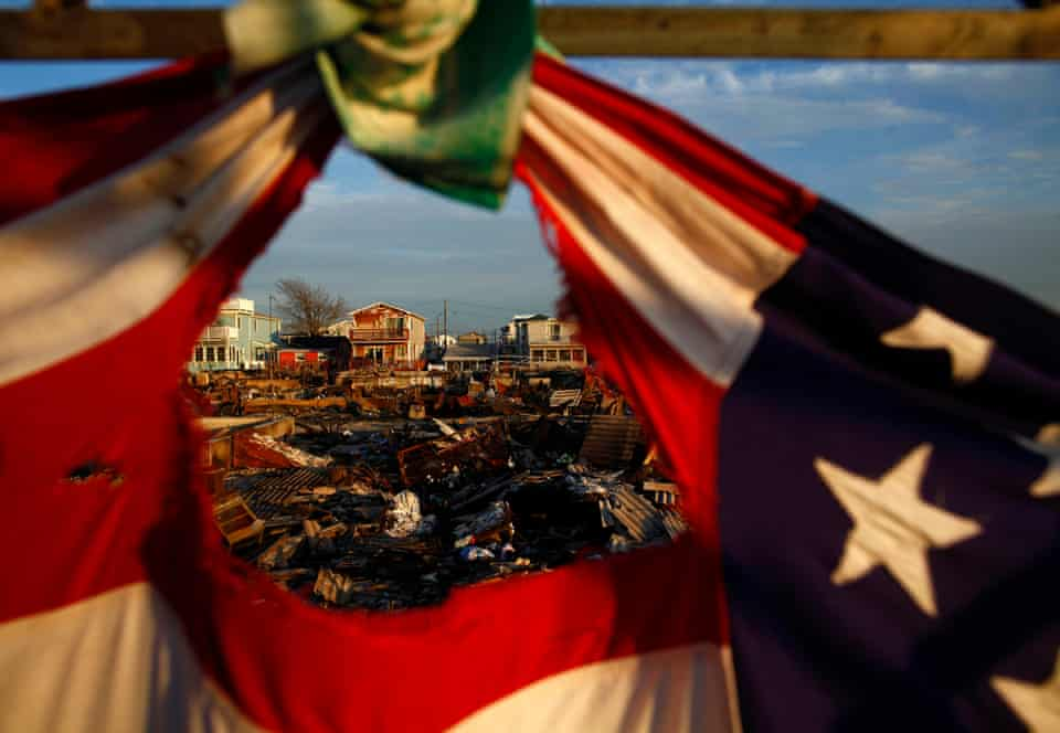 Homes destroyed during Hurricane Sandy are framed by a tattered American flag.