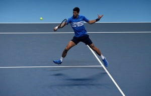 A leaping Novak Djokovic plays a backhand.