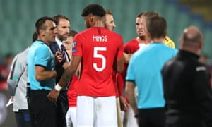 Tyrone Mings speaks to the referee Ivan Bebek during one of the stoppages in Sofia.