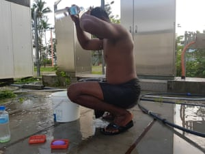 A refugee uses a bottle of water to wash himself at the Manus Island camp