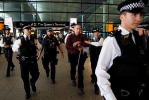London, England: Police officers detain environmental activist James Brown at Heathrow Terminal 2