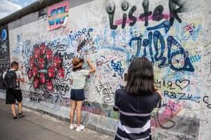 Visitors write on a graffiti wall