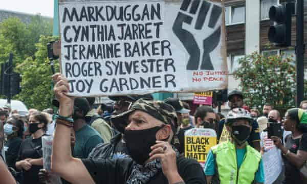 A protester holds a sign with Mark Duggan's name on it to mark the 2020 anniversary of the riots.