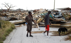 People walk among debris at the Mudd neighborhood, devastated after Hurricane Dorian hit.