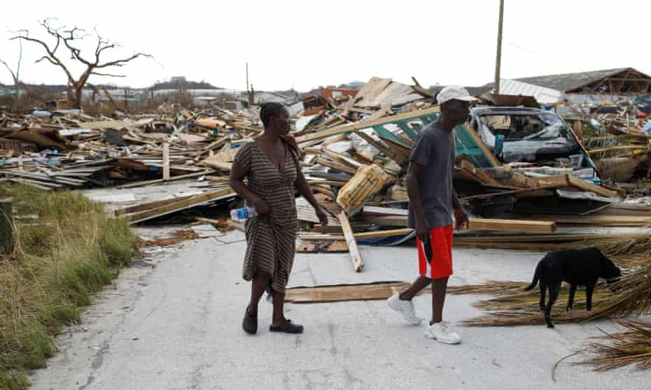 People walk among debris at the Mudd neighborhood, devastated after Hurricane Dorian hit.