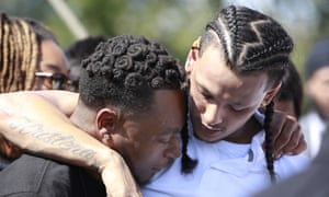 Mourners comfort each other at the gravesite of Stephon Clark after his funeral.
