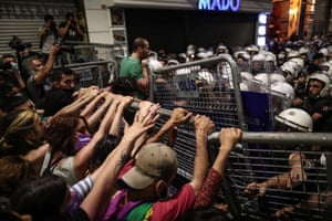 Protestors try to pull down metal fences in front of a mass of police