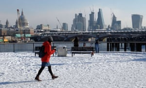 a woman walks through the snow with the city of london skyline in the background