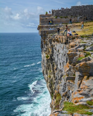 Tourists on Dun Aengus cliffs, Inishmore, IrelandHYT4R2 Tourists on Dun Aengus cliffs, Inishmore, Ireland