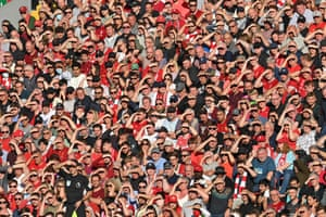 The assistant referee and Liverpool fans shield their eyes against the low sun