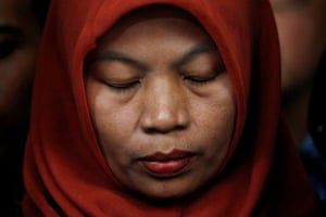 A teacher who was jailed after she tried to report sexual harassment reacts during a press conference in Jakarta, Indonesia
