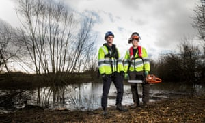 Men in high vis jackets, one with chainsaw