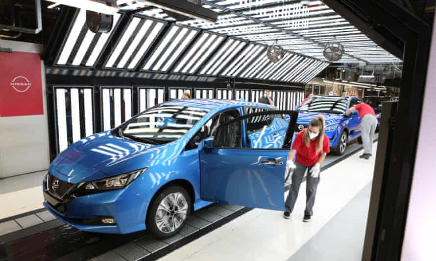 A worker in a brightly lit part of the production line attending to something on the open door of a modern looking blue hatchback