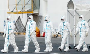 Workers wearing protective suits walk away from the cruise ship Diamond Princess