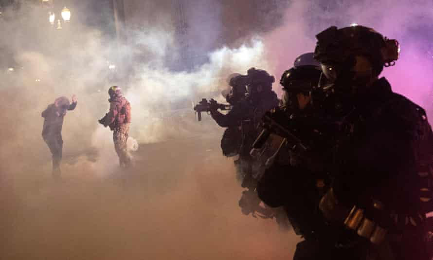 Federal law enforcement officers fire tear gas and other munitions to disperse protesters in Portland Wednesday night.