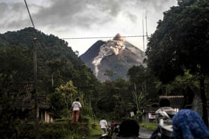 People look up at Mount Merapi, Indonesia's most active volcano, as it spews rocks and ash.