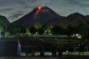 People gather to watch as lava flows down from the crater of Mount Merapi in Pakem, Hargobinangun, Yogyakarta