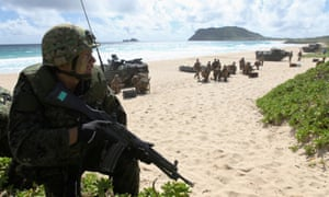 A Japanese soldier sets up a perimeter defence during a simulated beach assault.