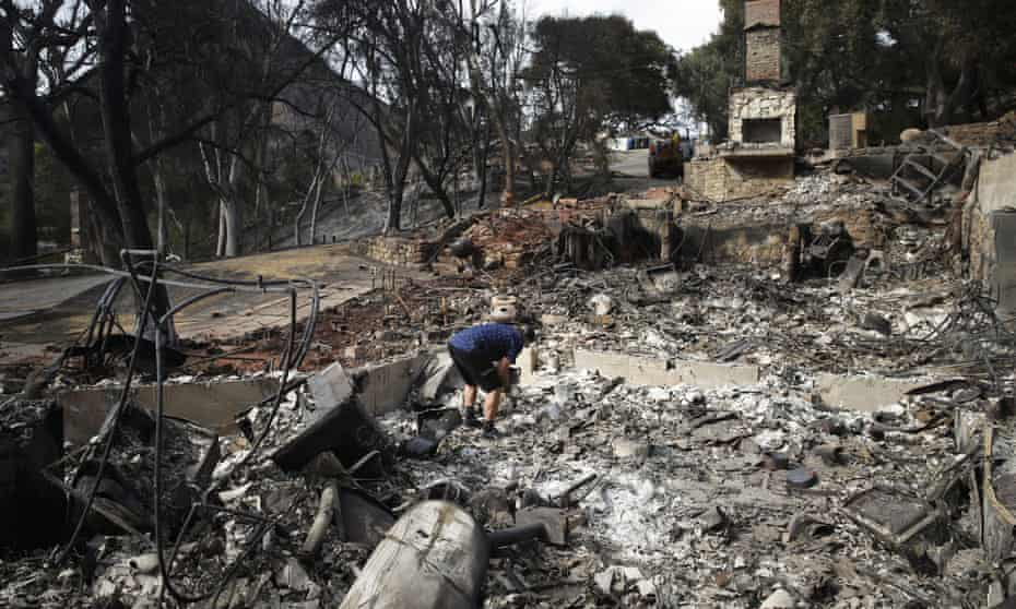 Roger Kelton searches through the remains of his mother-in-law's home leveled by the Woolsey Fire, in Agoura Hills, near Cornell, California.