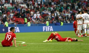 The Russian players are dejected whilst the Mexican players celebrate.
