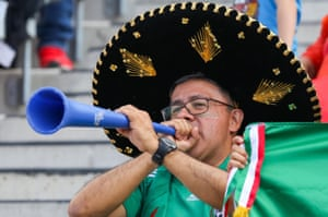 A fan wearing a sombrero cheers on Mexico with his vuvuzela