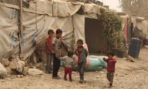 Syrian refugees stand outside tents at a camp in Bar Elias, Lebanon