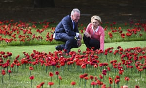 The director of the Australian War Memorial Brendan Nelson and German Defence Minister Ursula von der Leyen take a look at a field of handmade poppies in the sculpture garden of the Australian War Memorial