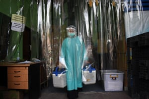 A health worker delivers containers of Covid-19 vaccines from a cold room in Bandung, Indonesia