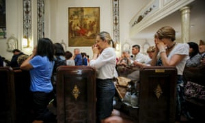People pray during mass