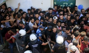Migrants and refugees are hemmed in by riot police at a stadium on Kos on 12 August.