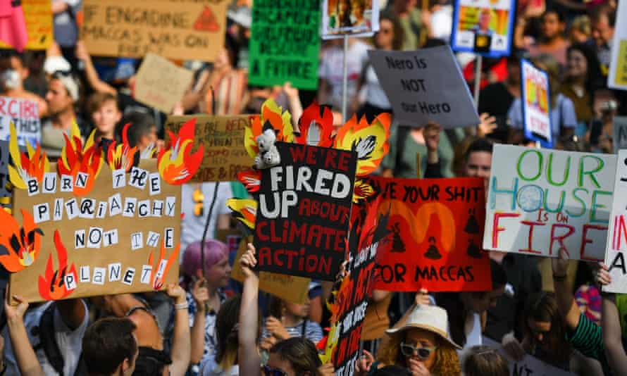 Climate change protesters hold up placards