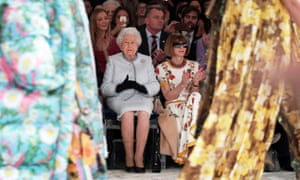 Queen Elizabeth II sitting next to Vogue's Anna Wintour in the front row, clapping, at Quinn's show, floral material drapes either side of them.