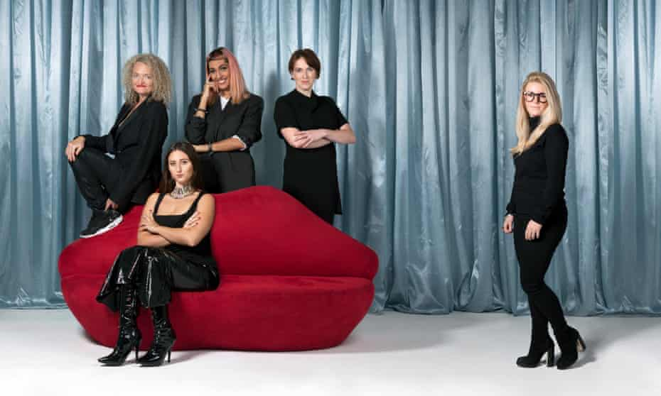 A red lips sofa with five women dressed in black, three standing behind it, one sitting on it and the other to one side