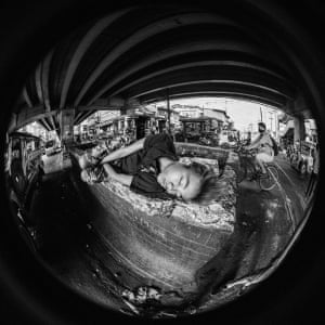 A homeless boy sleeps amid the cacophony of Manila's commuter traffic