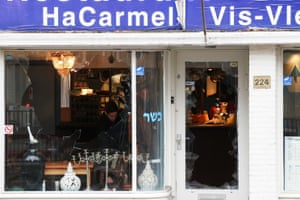 A kosher restaurant in Amsterdam cleans up after its wndows were smashed.