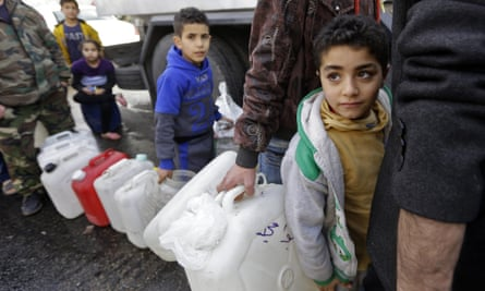 Syrians wait to fill plastic containers with water