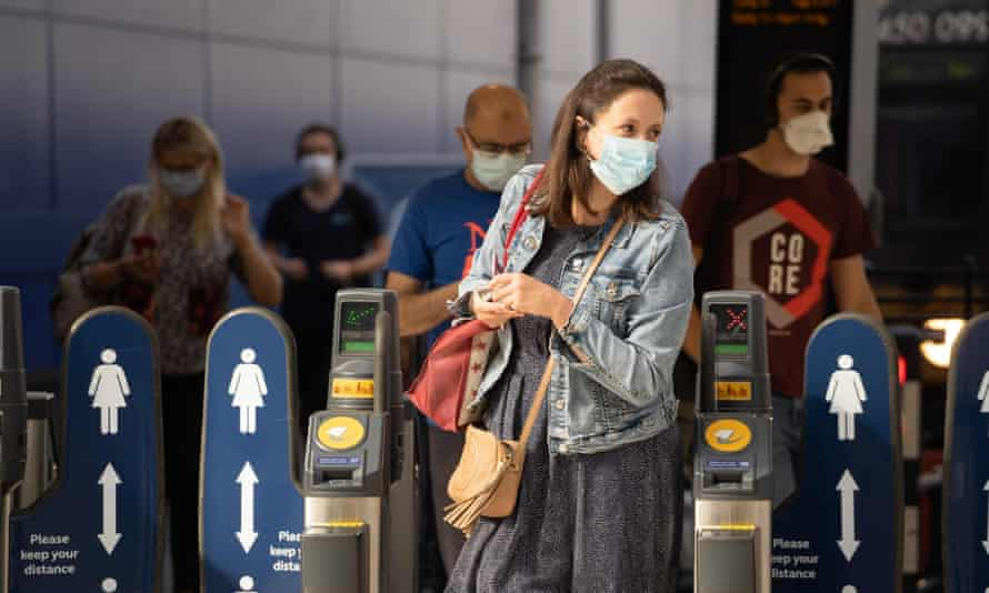 Commuters wearing face masks walk through the ticket barriers at Waterloo Station in London