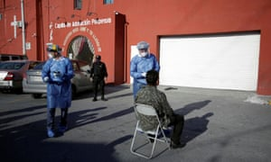 """A medical worker talks with a patient outside the migrant shelter """"Casa INDI"""", where some migrants have been infected with coronavirus in Monterrey, Mexico 12 June 2020."""