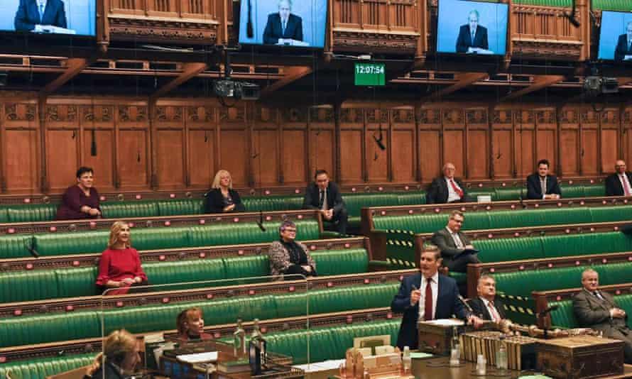 Keir Starmer speaks as big screens display an image of the video-linked Boris Johnson.